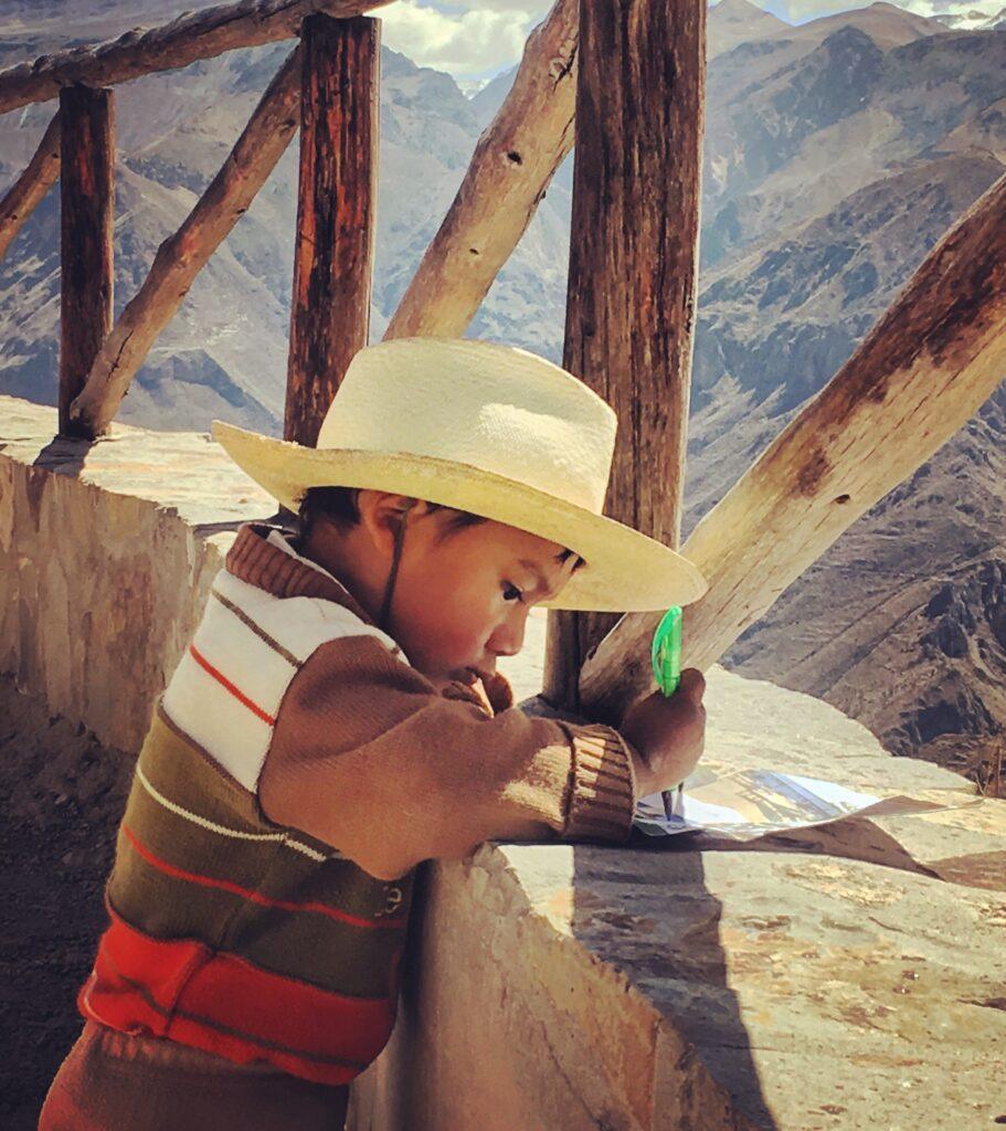 Bambino peruviano intento a disegnare le montagne